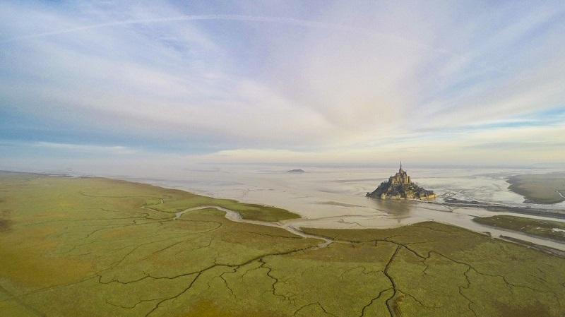 """عکاس، منظره ی مونت سنت مایکل را در ساعت 5 صبح و در حالی نشان می دهد که آب به دلیل جزر آن را احاطه کرده است. این مکان در جزیره ی نورماندی فرانسه واقع شده است. عکس """"مونت سنت مایکل"""" مقام دوم را در دسته ی """"مکان ها"""" به خود اختصاص داد."""