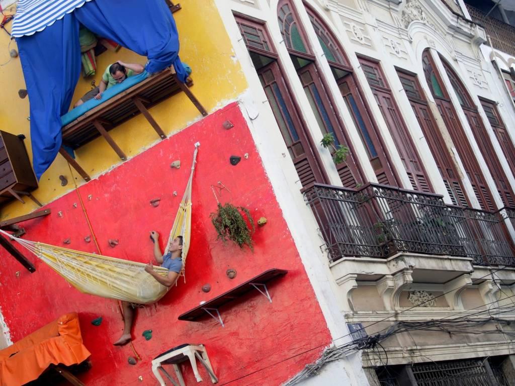 هنرمند برزیلی، تیاگو پریمو (طبقه ی بالایی) و برادرش گابریل در ریو دوژانیرو، یک خانه ی عمودی را روی یک دیوار صخره نوردی ساخته اند. آنها در این خانه از قفسه، پیشخوان و تخت خواب بهره مند بودند اما از سرویس بهداشتی گالری هنری همسایه استفاده می کردند.