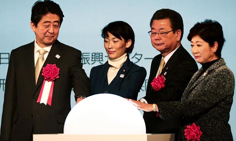 شینزو آبه، نخست وزیر ژاپن (سمت چپ) به همراه دیگر مقامات ژاپنی طی مراسمی دست های خود را بر روی کره شیشه ای (حاوی رنگ های مختلف لوگوی المپیک) قرار دادند، تا عملیات احداث ورزشگاه المپیک 2020 توکیو رسما آغاز شود.