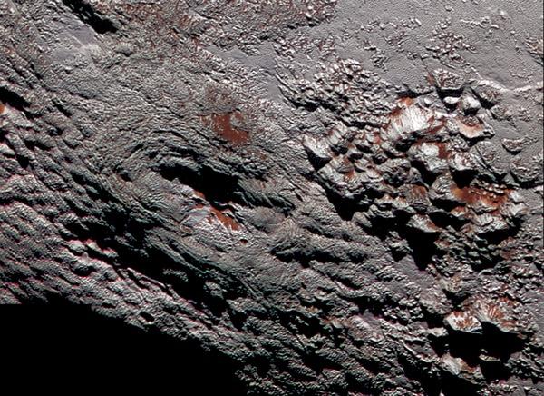 """در عکسی که مشاهده می کنید، کاوشگر نیوهورایزنز نمای خارقالعاده و نزدیکی از سطح پلوتو را نشان می دهد که در آن یکی از دشت های پر چاله پلوتو به کوهستانی بلند رسیده است. در این عکس کوهستان های """"کرون ماکولا""""دیده میشود که حدود ۲٫۵ کیلومتر ارتفاع دارند. این رگه های مایل به سرخ، از ترکیبهای پیچیدهای به نام تولین پوشیده شده اند."""