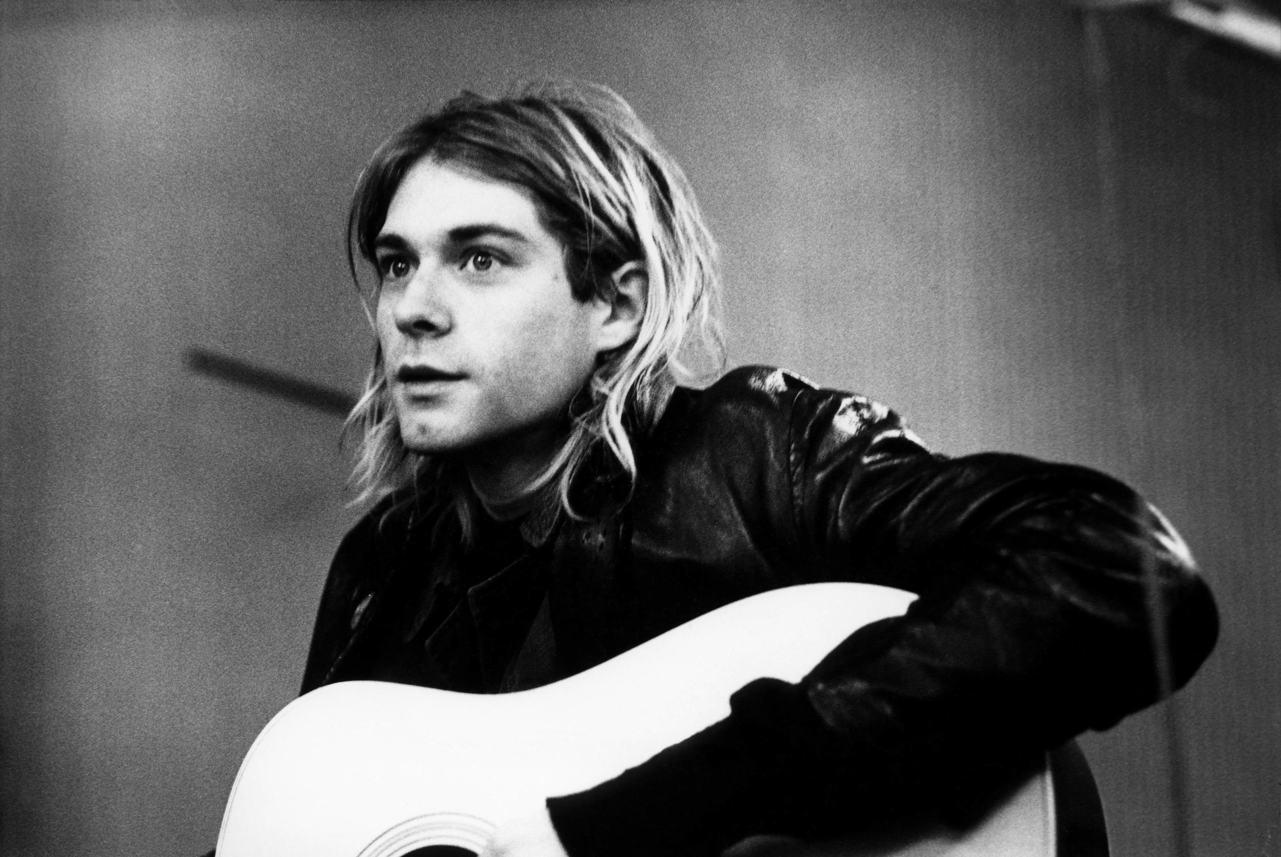کرت کوبین در حال نواختن گیتار آکوستیک