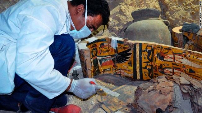 یکی از اعضای تیم باستان شناسی مصر در حال کار بر روی یکی از تابوت های چوبی به تازگی کشف شده