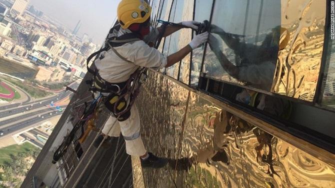 کارگری در حال نصب روکش استنلس استیل طلا. در طرح دونیس پیشنهاد شده بود، قاب دبی 150 متر ارتفاع داشته باشد، همان ارتفاعی که شهرداری دبی سازه خود را ساخته است، عرض قاب فعلی تنها 12 متر است که از طرح اصلی کمتر است