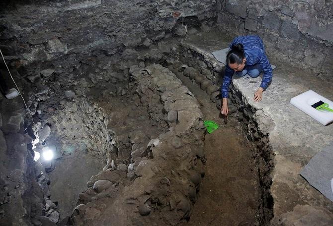 باستانشناسی از موسسه ملی انسانشناسی و تاریخ مکزیک (INAH) در محل کشفیات اخیر در مکزیکوسیتی. باستان شناسان هنوز تلاش میکنند به پایه برج جمجمه و بسیاری از جمجمههای دیگر که ممکن است در این محل باستانی نهفتهاند برسند