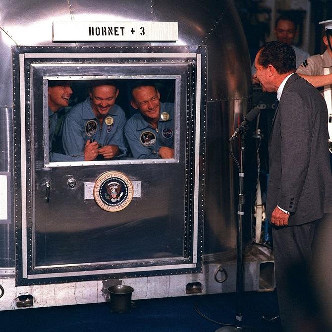 ریچارد نیکسون با استفاده از یک میکروفون در حال گفتگو با فضانوردان مأموریت آپولو11. زمانی که خدمه آپولو 11 از فرود پیروزمندانه خود در ماه بازگشتند، ناسا پس از فرود فضانوردان در اقیانوس آنها را به یک مرکز سربسته در هیوستون برد، جایی که آنها به مدت دو هفته به روشهای مختلف پاکسازی شدند