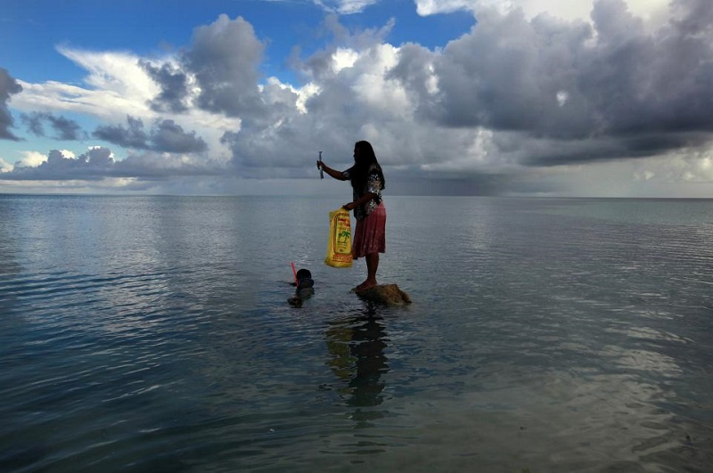 """زنی که روی تخته سنگ ایستاده و ماهی در دست دارد """"بیناتا پیناتا"""" نام دارد. در ۲۵ مارس ۲۰۱۳، """"کایباکیا"""" همسر بیناتا، در جزیره کوچک بیکمن در مجمع الجزایر کیریباتی واقع در اقیانوس آرام گرفتار شد. رئیس جمهور کیریباتی، آنوته تونگ، پیشبینی میکند که طی ۳۰ تا ۶۰ سال آینده، بدلیل افزایش سطح آب دریاها که ناشی از طغیان و آلودگی منابع آب شیرین است، کشور او غیرقابل سکونت خواهد بود."""