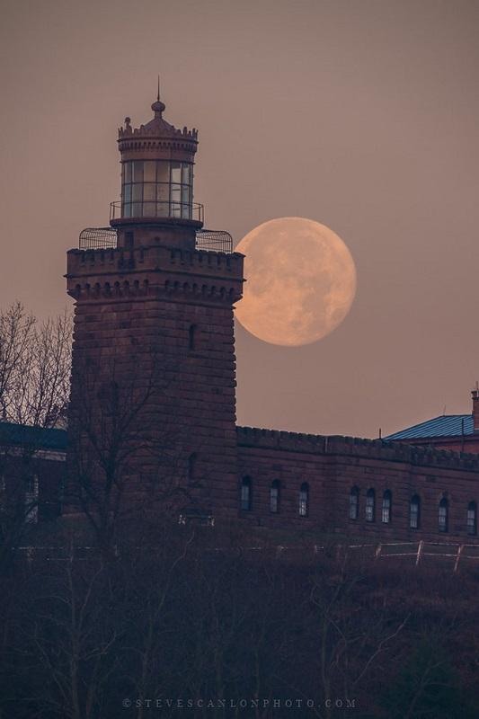تصویری از برج جنوبی توین لایتز (Twin Lights) در ایالت نیوجرسی، که در دوشنبه ۱۴ آذر، توسط استو استانلون (Steve Scanlon) گرفته است. ماهی که در پشت این برج پیداست ۲۴ ساعت از حالت بدر کامل فاصله دارد.