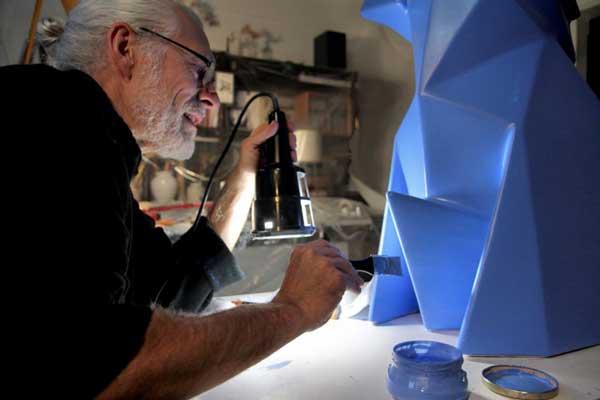 جیمز پرونیر، طراح و مجسمهساز در حال رنگآمیزی خرگوش پاپیه ماشه با رنگ آبی کبالت