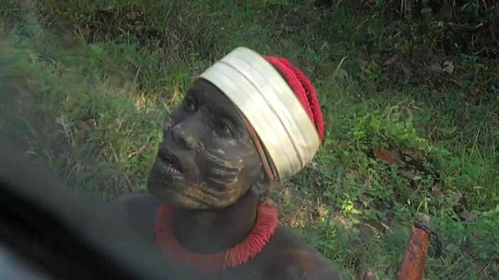 نمایی از اتوبوس سافاری انسان، در این تصویر یکی از گردشگران به یکی از اعضای قبیله جاوارا آبنبات میدهد